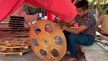 Large cutouts of film reel models get spray painted in gold and jewel blue ahead of IFFI 2019 in Goa.