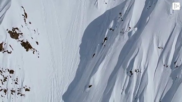 A man falls dozens of meters down a mountain with his skis
