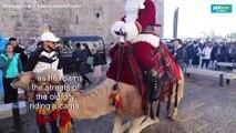 Santa Claus visits Jerusalem on camelback
