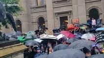Melbourne demonstrators shelter under hundreds of umbrellas at climate protest