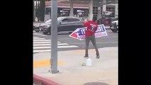 Il manie son panneau publicitaire comme un roi... un vrai artiste de rue