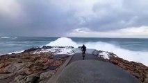 Ce cycliste se rapproche un peu trop près du bord de mer pendant la tempête en Espagne