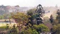 Un hélicoptère atterrit et recouvre de poussière une autoroute