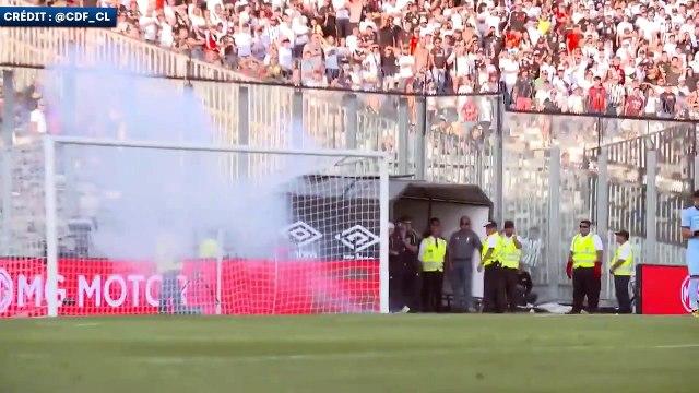 Un gardien ramasse un téléphone portable lors du chaud derby de Santiago au Chili