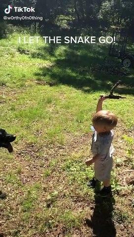 Un enfant attrape un serpent à la main et le jette à son chien... Va chercher