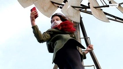 Menina sobe em moinho de vento para enviar lição de casa via Internet durante isolamento