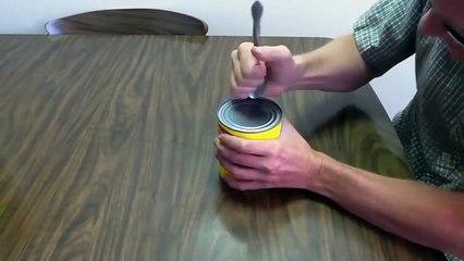 Il vous montre comment ouvrir une boite de conserve avec une cuillère