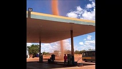 Une mini tornade de sable passe juste à côté d'une station essence