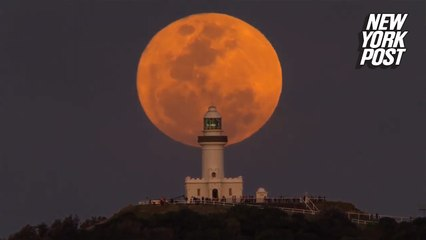 Red moon rising over lighthouse is an out-of-this-world view