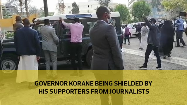 Governor Korane being shielded by his supporters from Journalists