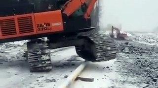 Ce conducteur de pelleteuse chevauche un tuyau avec son engin... doué